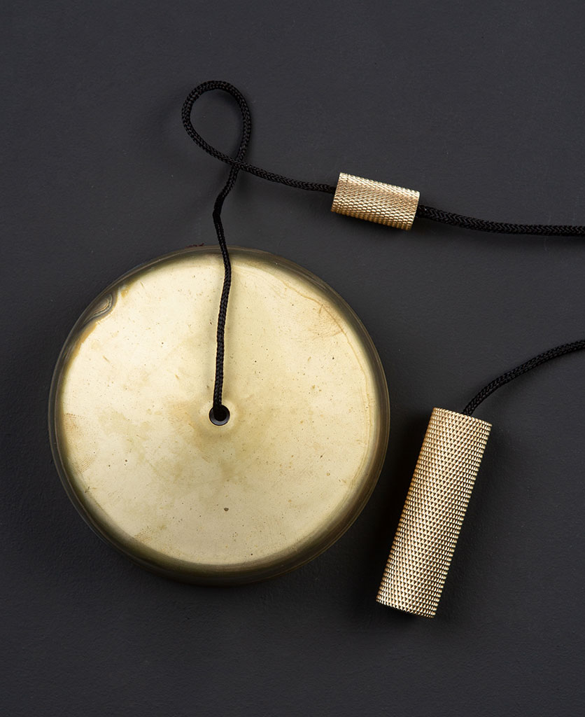 smoked gold pull cord switch with brass pull against black background