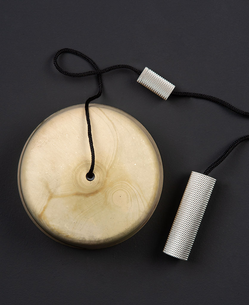 smoked gold pull cord switch with silver pull against black background
