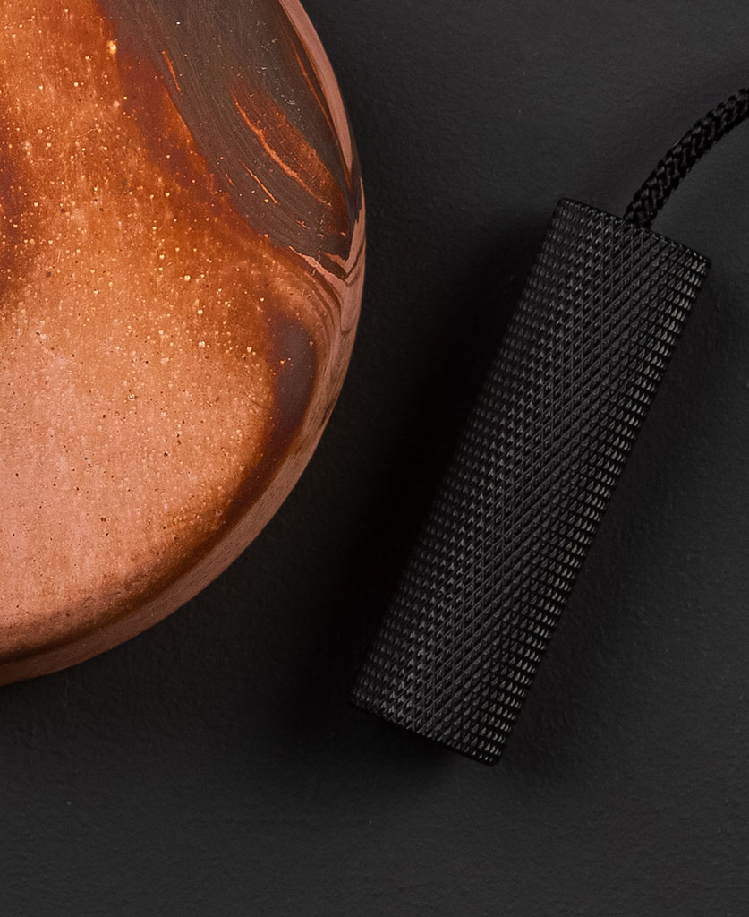 tanrished copper pull cord switch with copper ceiling rose and black pull against black background