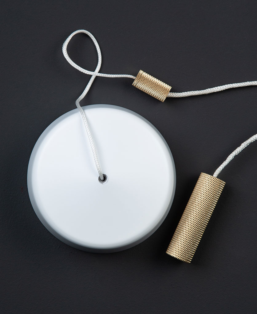 White pull cord switch with brass pull against black background