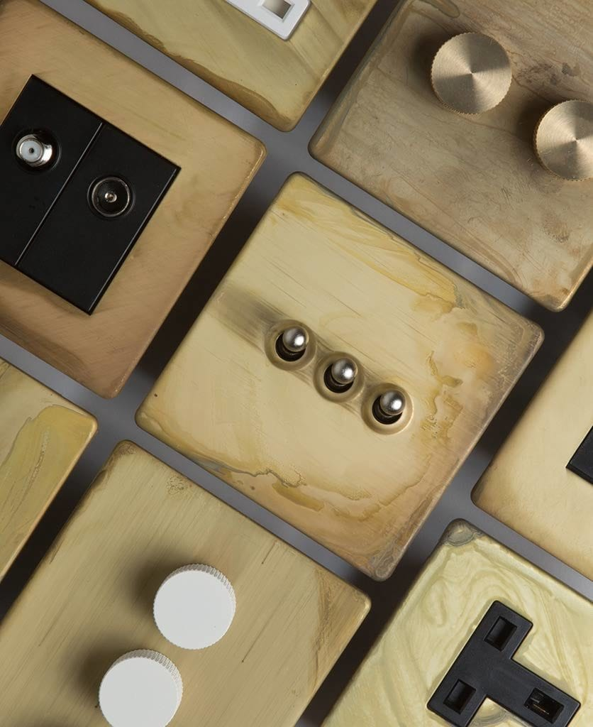flatlay of smoked gold dimmers, toggles and sockets against grey background