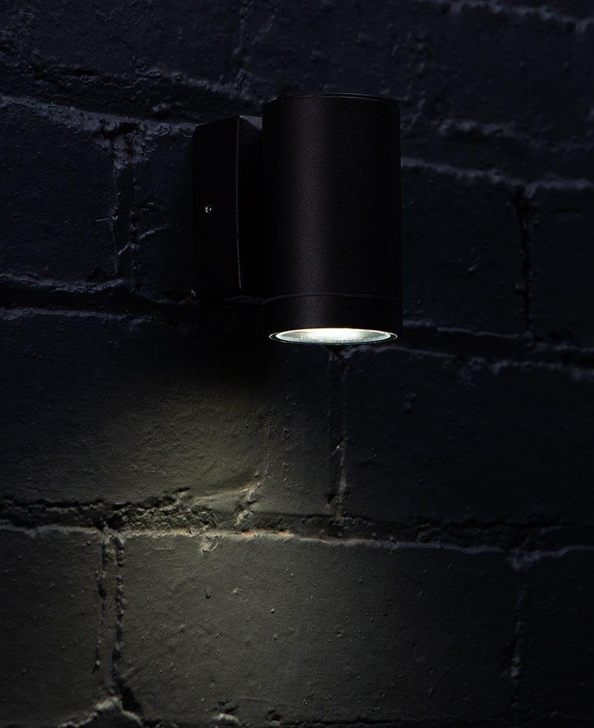 capella black garden light against black brick wall