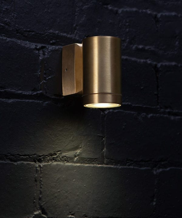 capella brass wall light against black painted brick wall