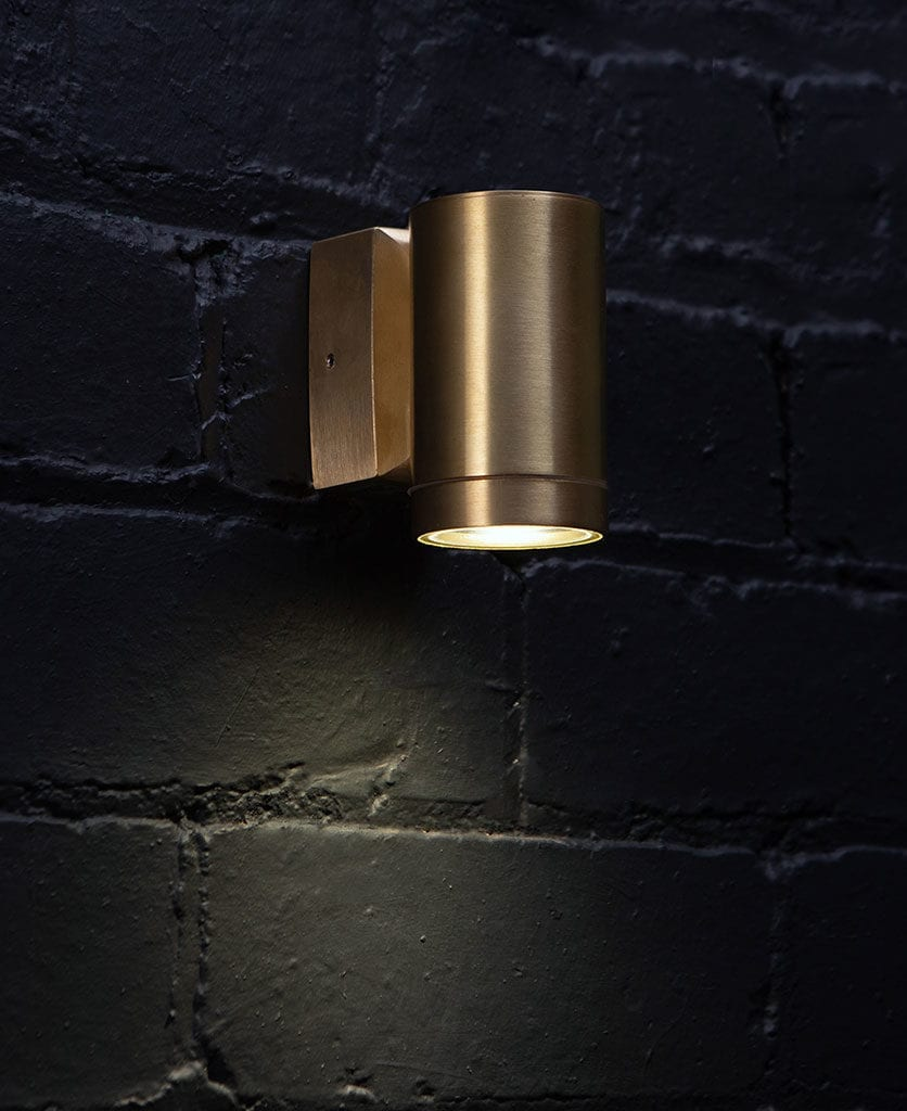 capella raw brass against black painted brick wall