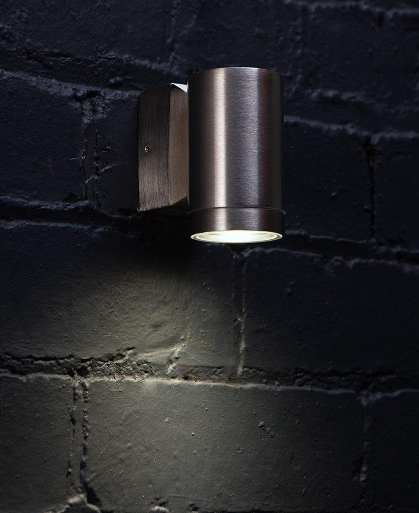 capella silver garden light against black brick wall