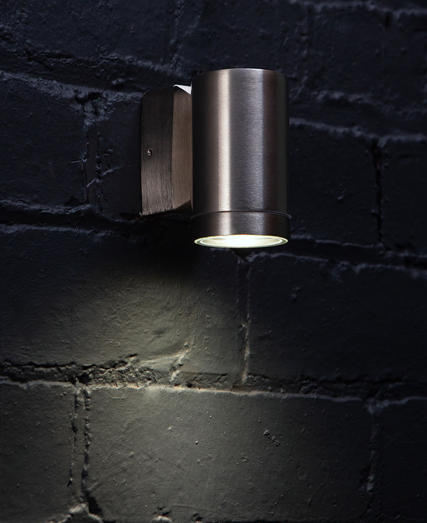 capella silver wall light against black painted brick wall