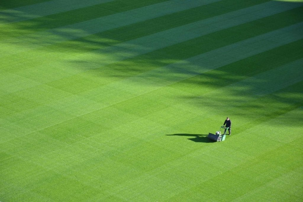 image of gardener mowing large green lawn