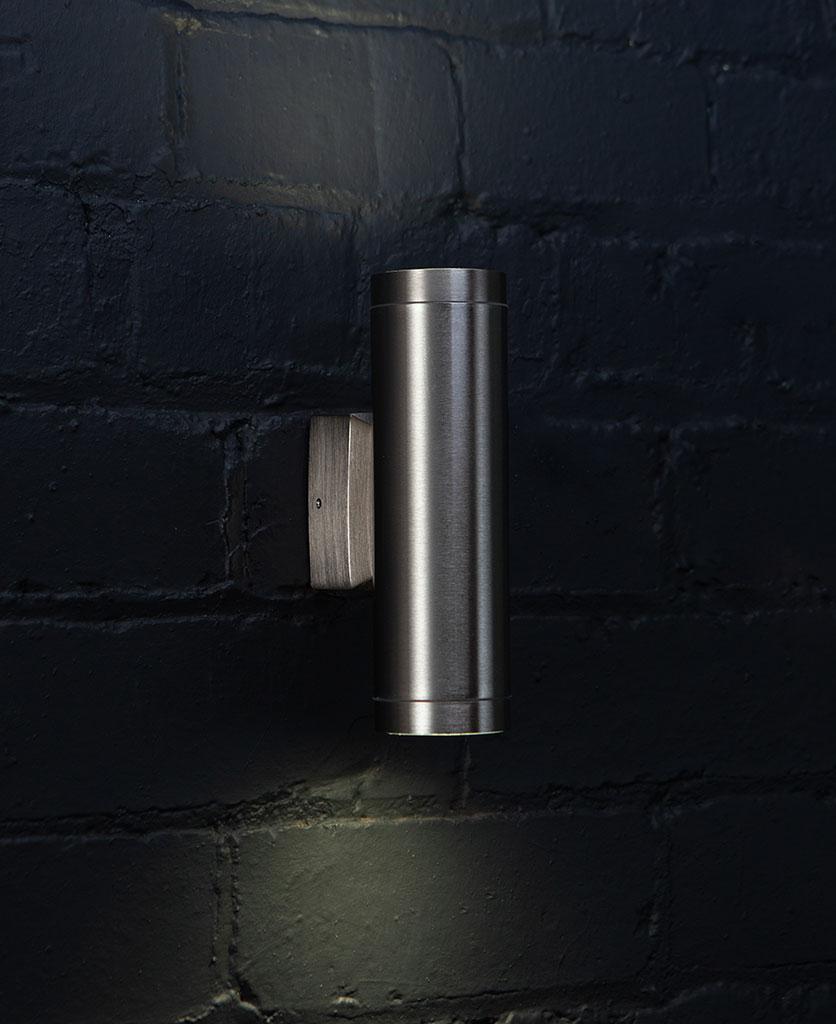vega tin silver wall light on black painted brick wall