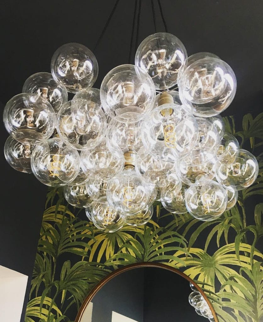 living room lighting clear bubble chandelier against tropical print wallpaper