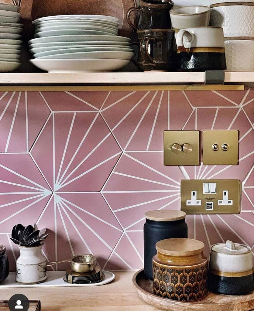 brass switches and sockets on pink and white tiled kitchen wall