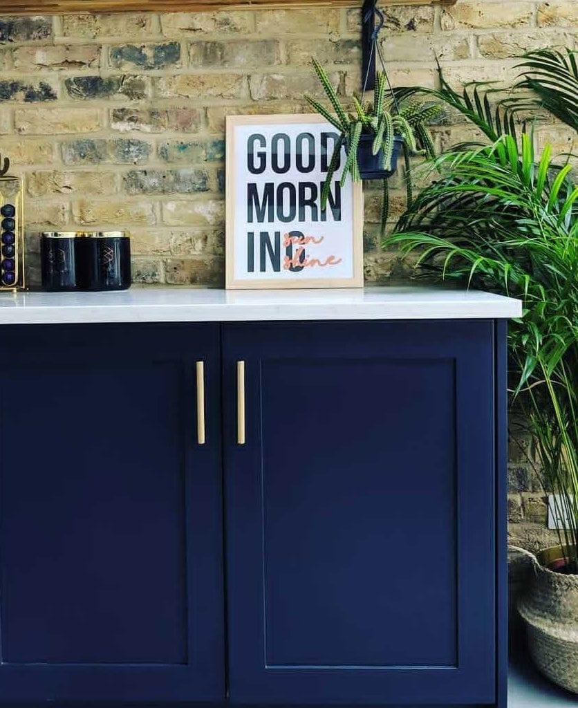 brass skyscraper handles on dark blue kitchen cupboards in an exposed brick kitchen
