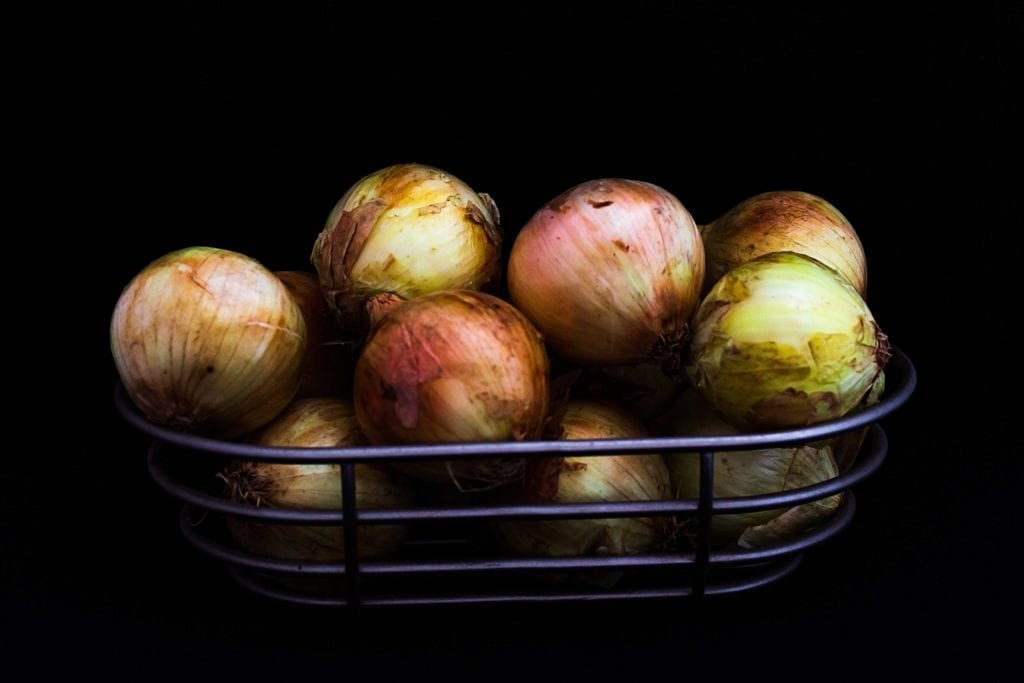 metal bowl holding freshly picked onions