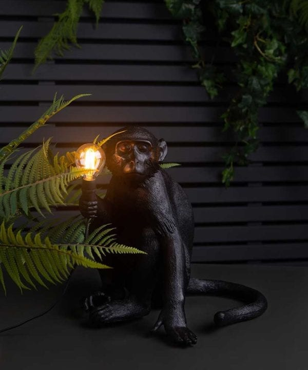 monty monkey light holding a lit bulb sat on top of a black table against black fencing