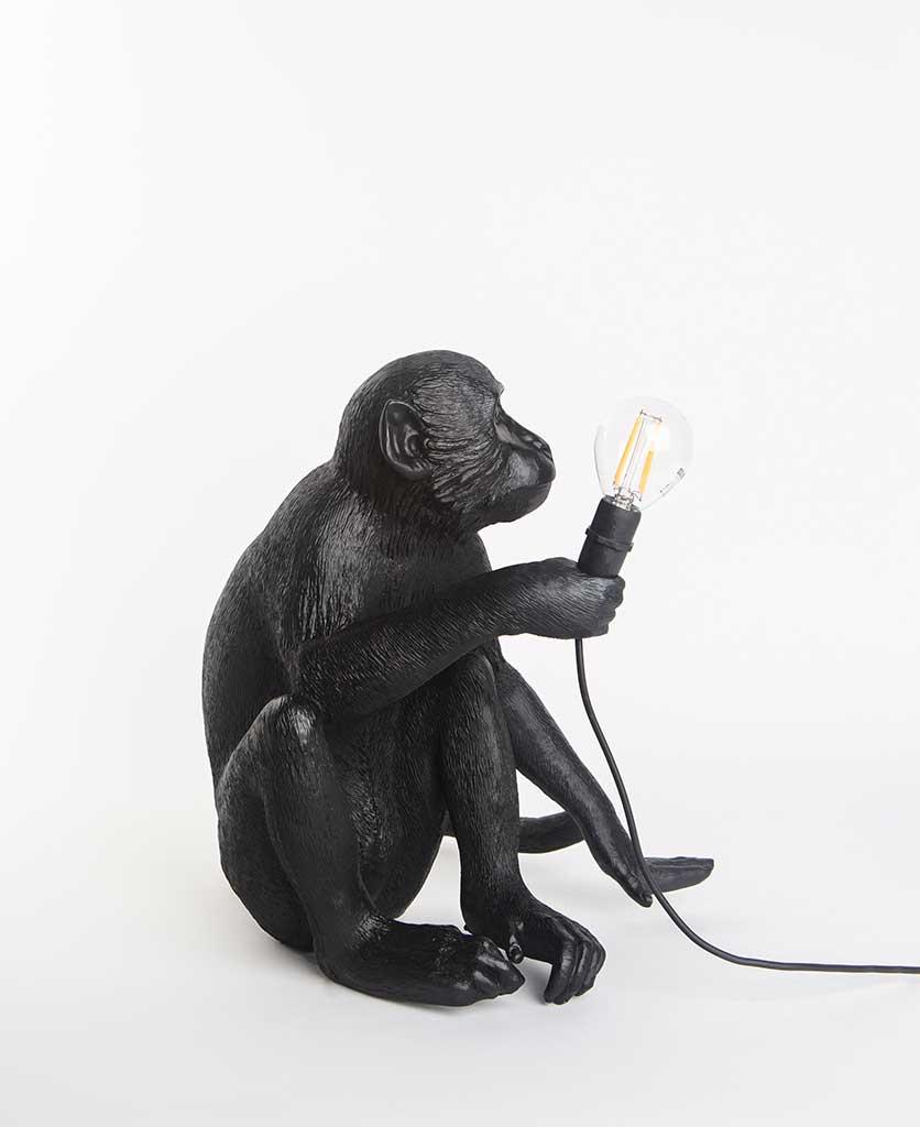 Abu sitting monkey black resin table lamp holding light bulb on white background