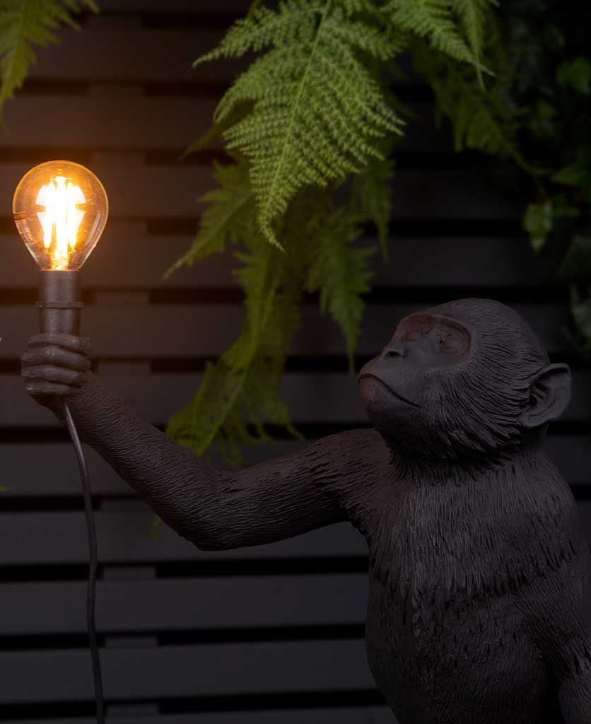 closeup of Buddy standing monkey black resin table lamp holding light bulb on black background with faux fern plant