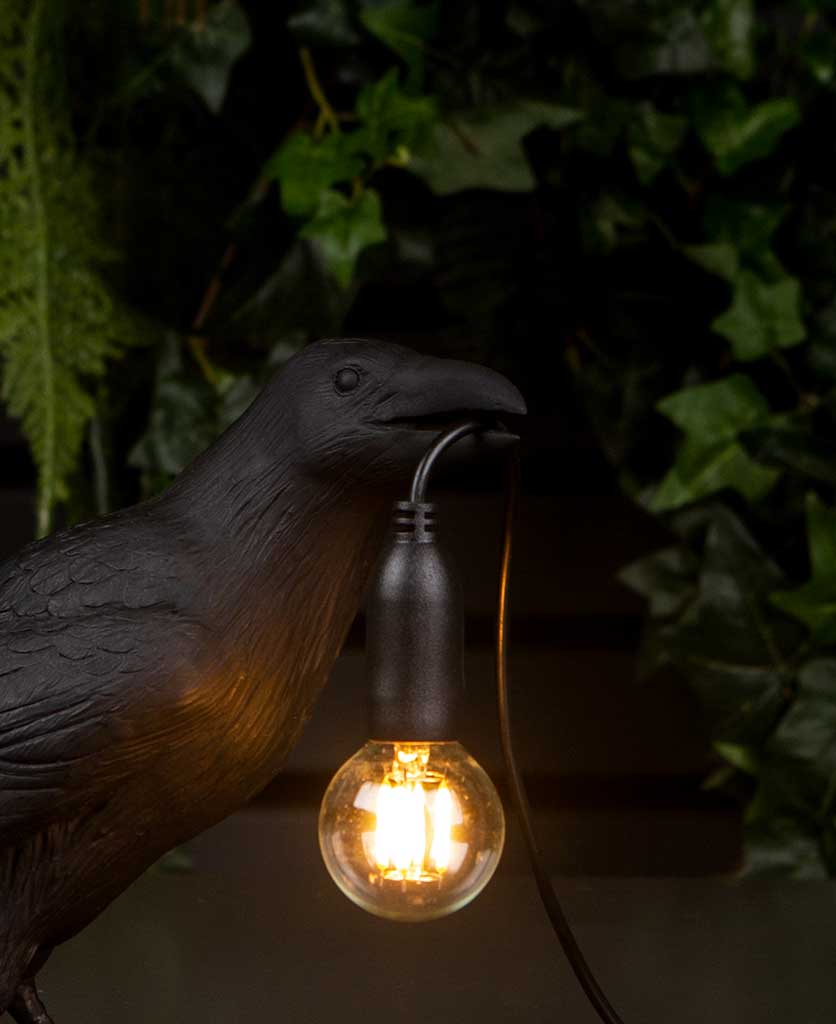 Close Up of Daphne Waiting raven black resin bird lamp holding bulb on black background with artificial plants
