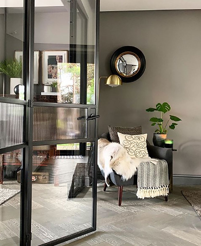 grey living room with crittal style doors and a monstera plant sitting on a coffee table