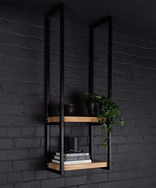 Knox steel shelves holding books and foliage against a black paintde brick wall
