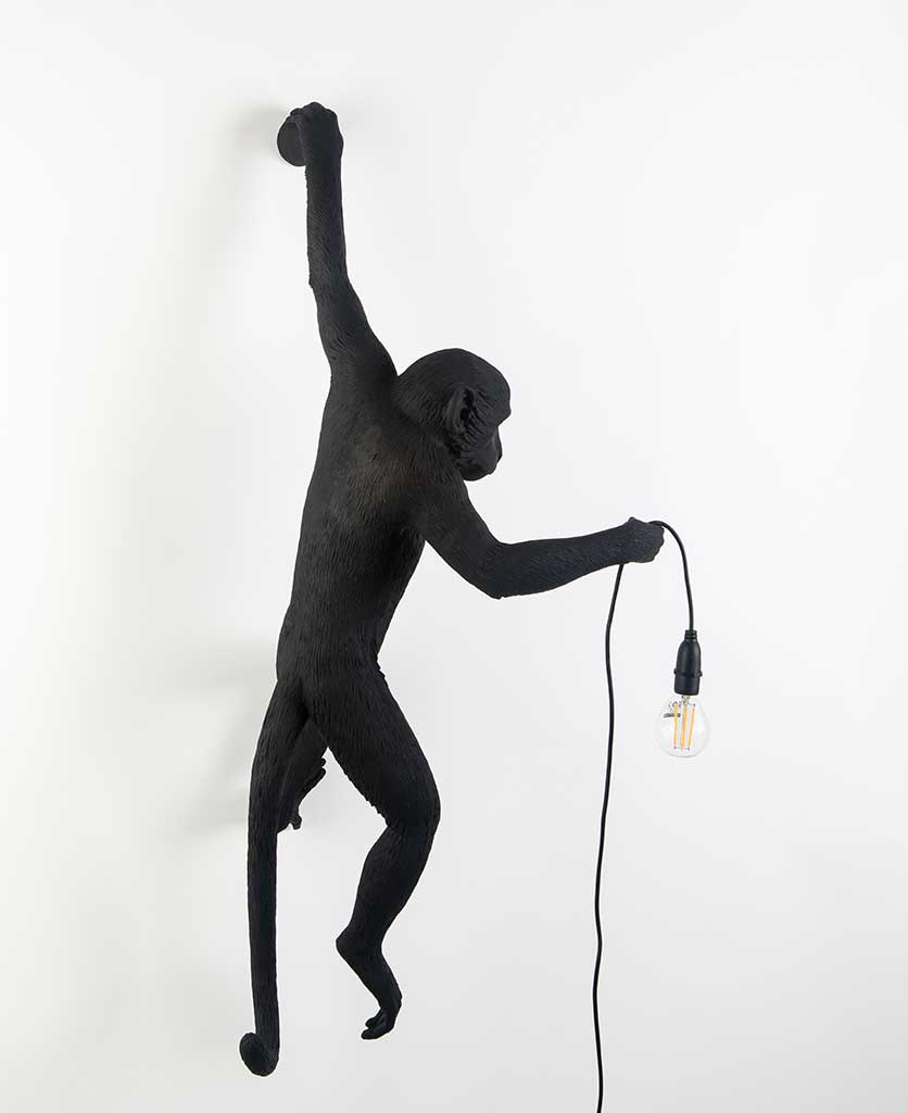animal light louie outdoor monkey light suspended against white wall