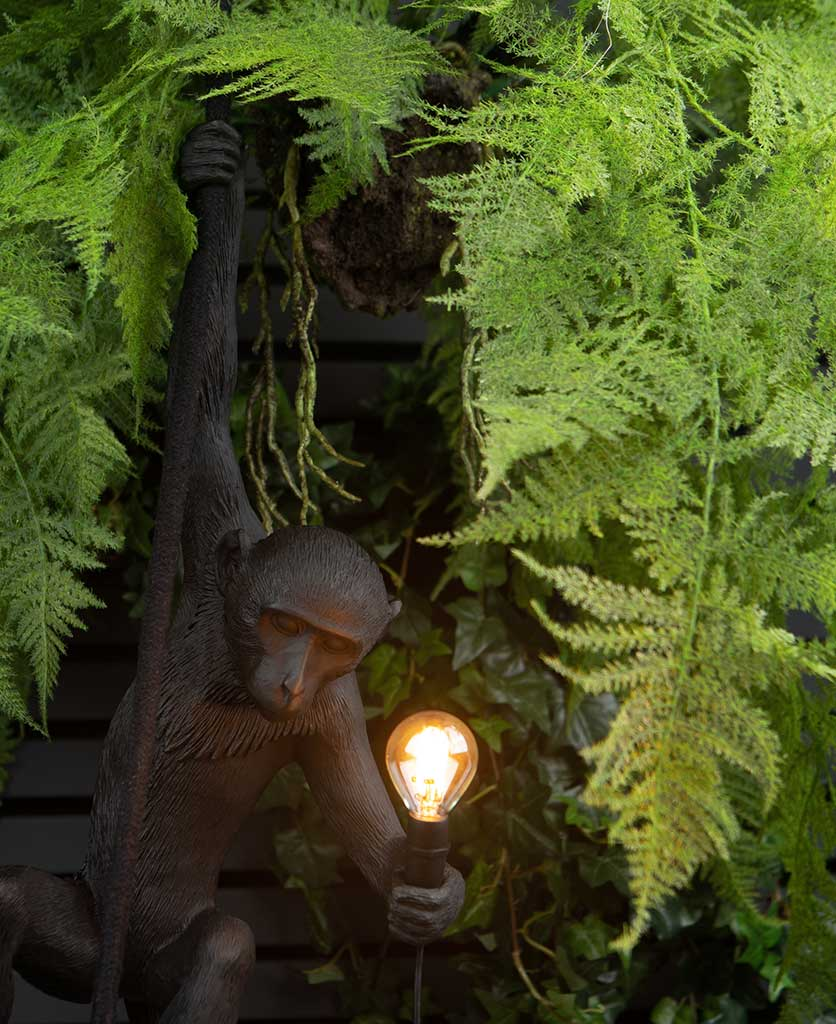 closeup of marcel monkey wall light surrounded by faux foliage