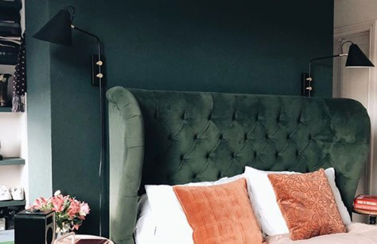 dark green velvet headboard against dark green wall