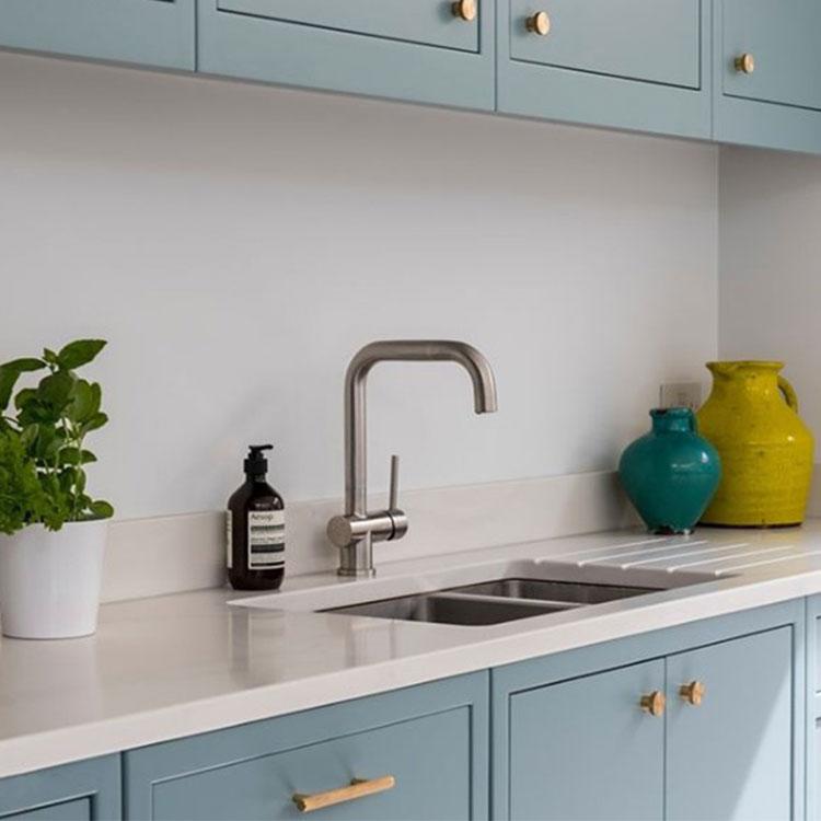 soft blue kitchen cupboards with brass door handles in white kitchen