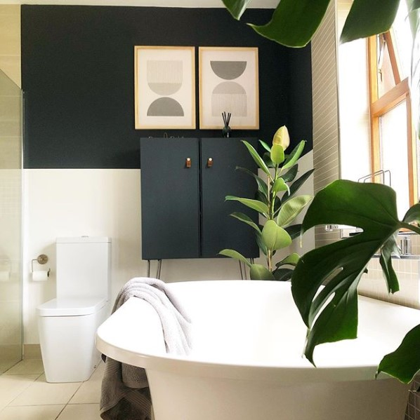 navy and white bathroom with large white bath and monstera plant