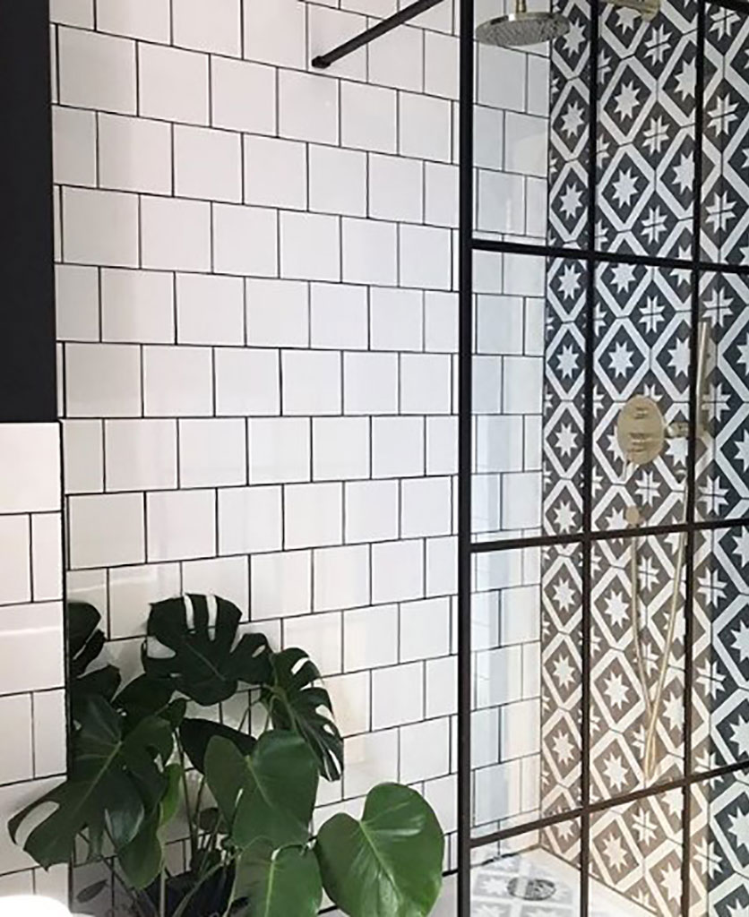 black crittal shower screen in white and black tiled bathroom with monstera plant