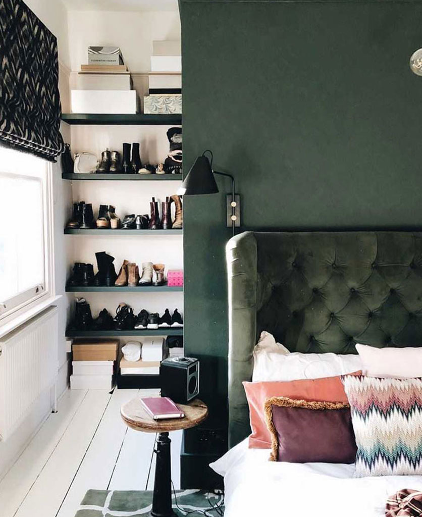 dark green painted wall with matching velvet headboard in a white and green bedroom