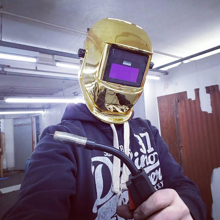 james wearing a gold welding helmet