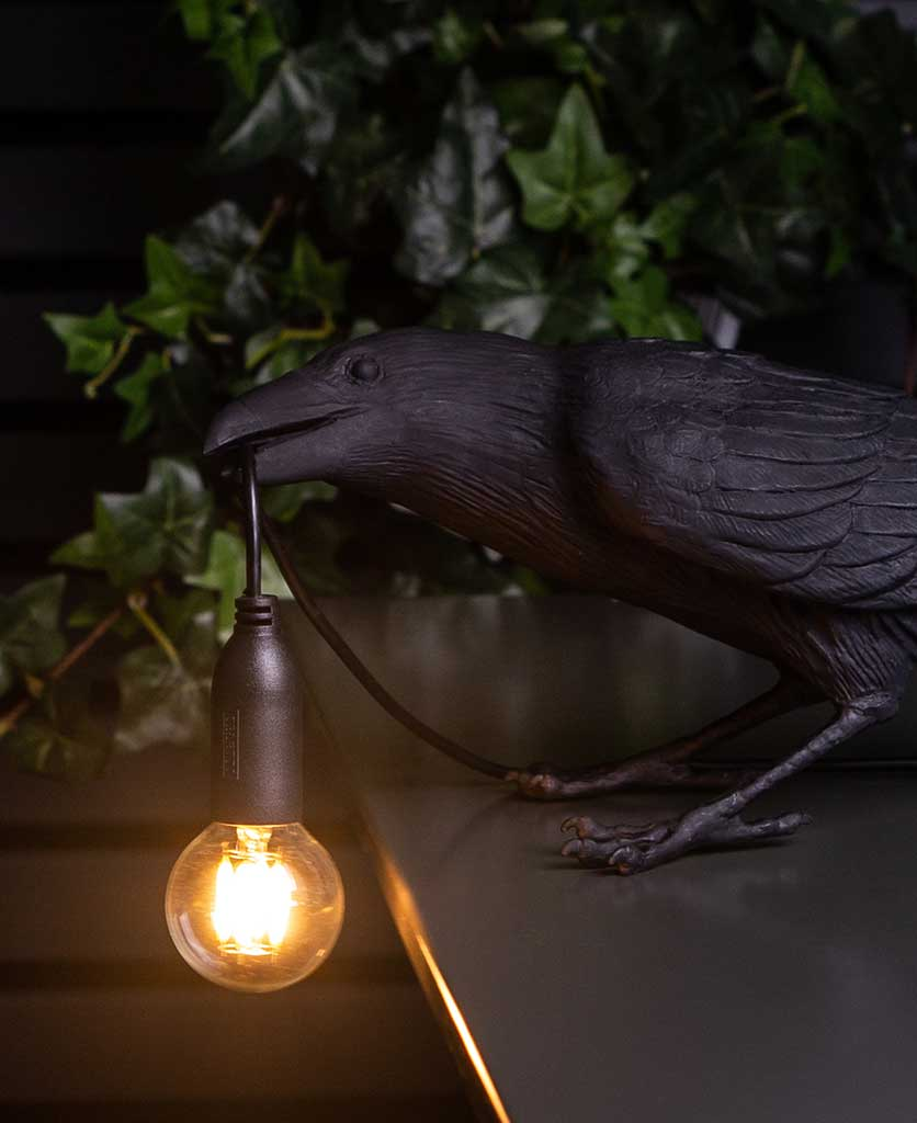 Close up of Alfred playing raven black resin table lamp holding bulb