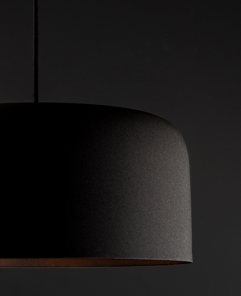 closeup black bodo kitchen pendant lighting suspended from black fabric cable against black wall