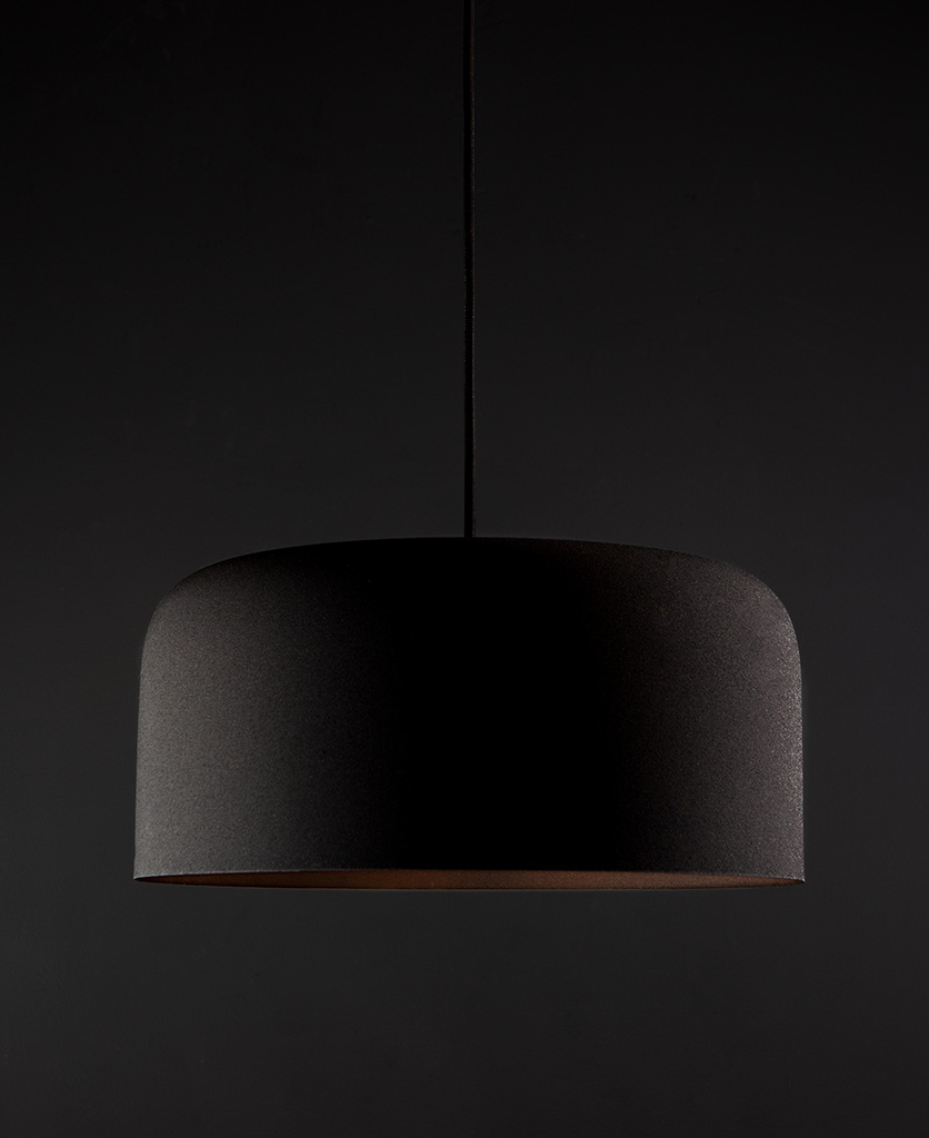 Large black bodo kitchen pendant lighting suspended from black fabric cable against black wall