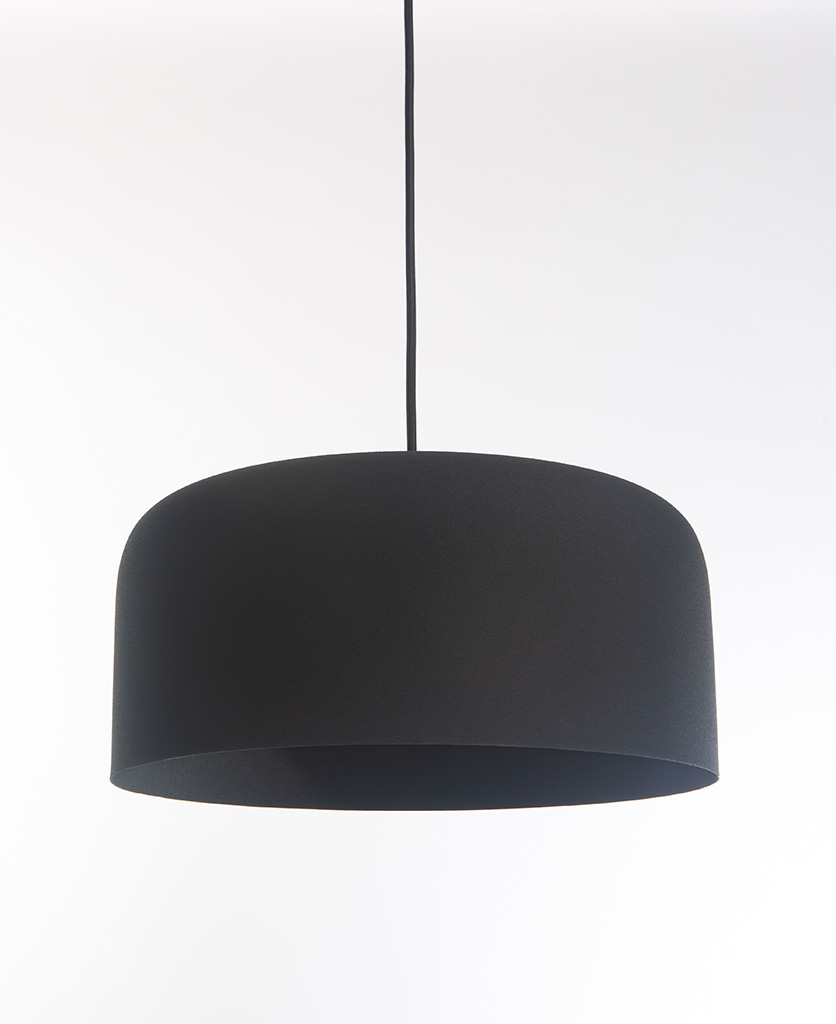 black pendant light suspended from black fabric cable on white background