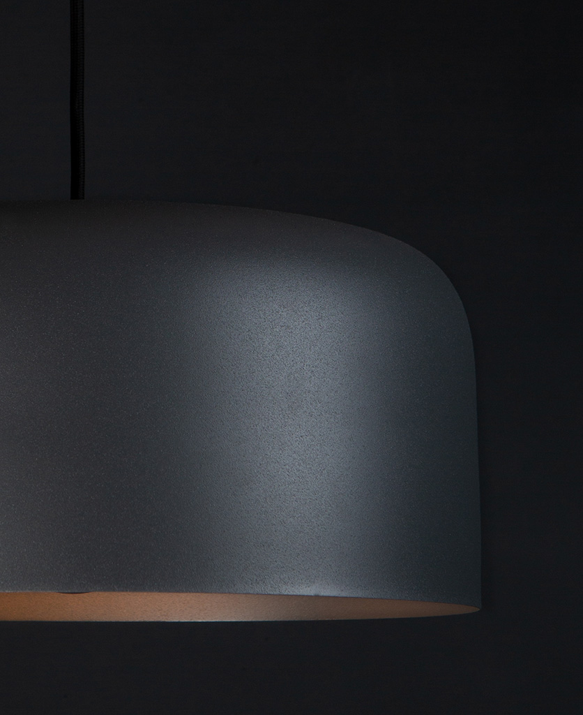 closeup grey bodo kitchen pendant lighting suspended from black fabric cable against black wall