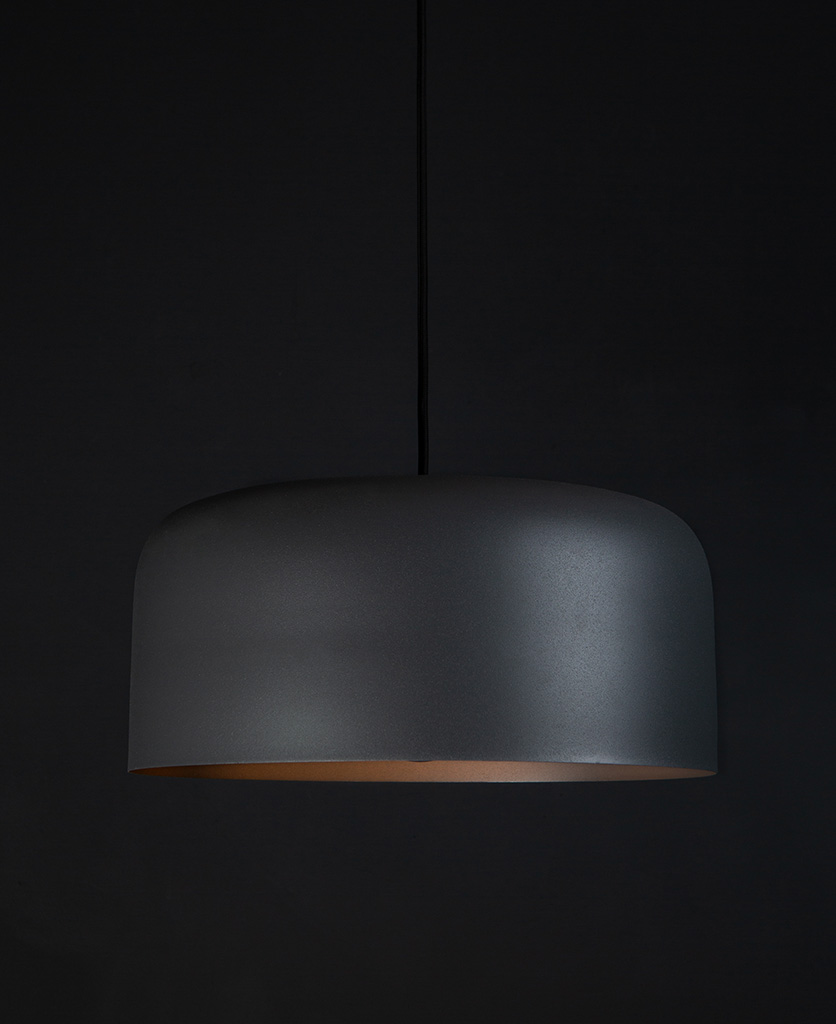 Large grey bodo kitchen pendant lighting suspended from black fabric cable against black wall