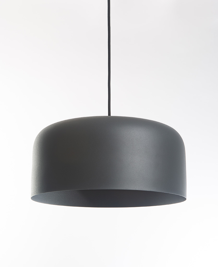 grey pendant light suspended from black fabric cable on white background