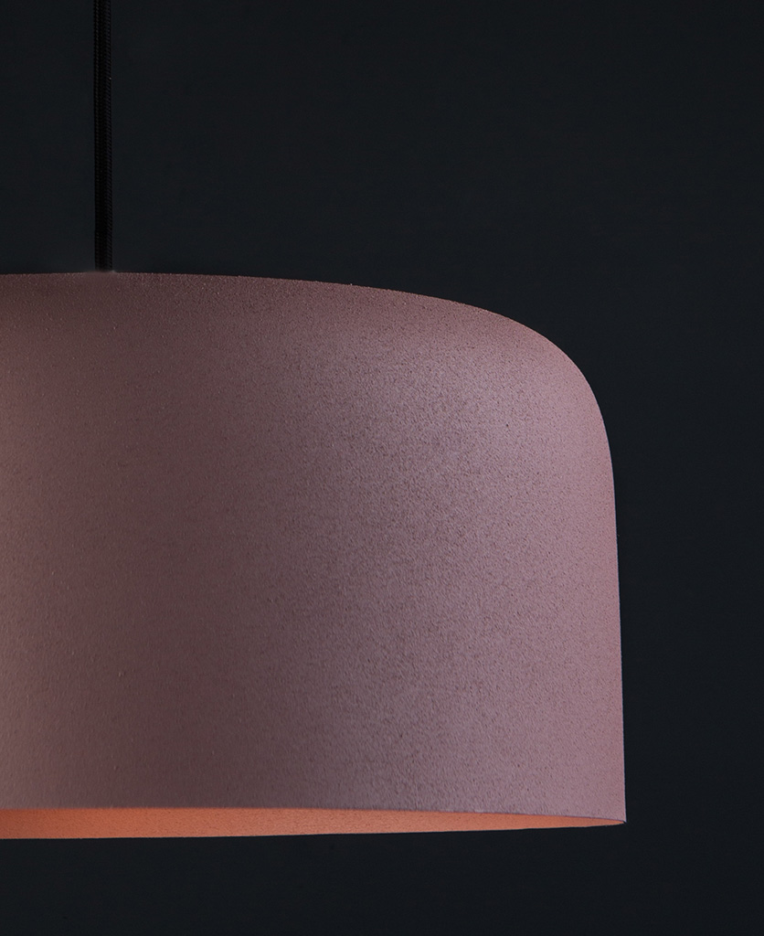 closeup pink bodo kitchen pendant lighting suspended from black fabric cable against black wall