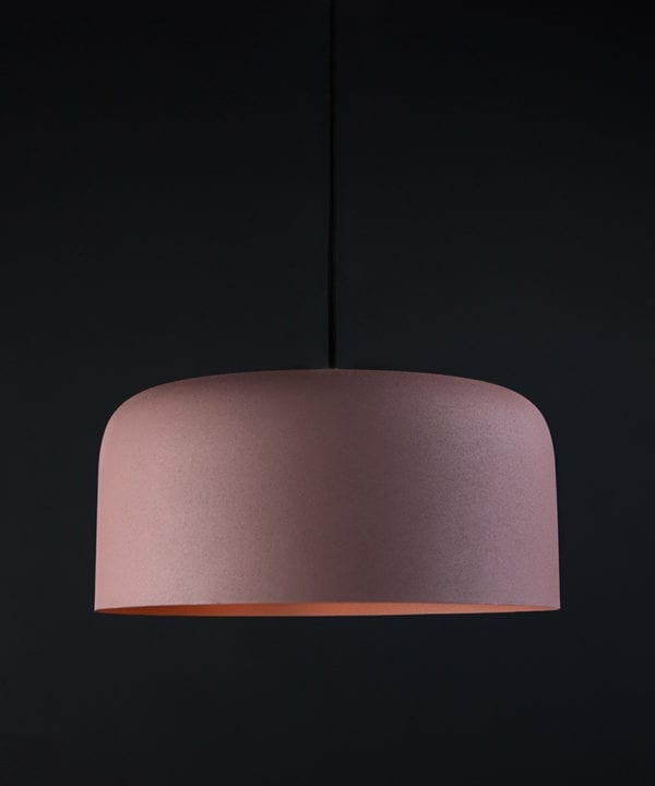 Large pink bodo kitchen pendant lighting suspended from black fabric cable against black wall