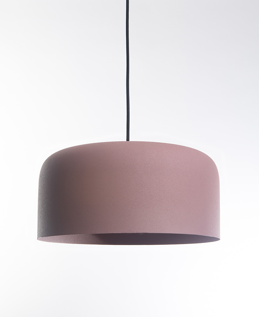 pink pendant light suspended from black fabric cable on white background