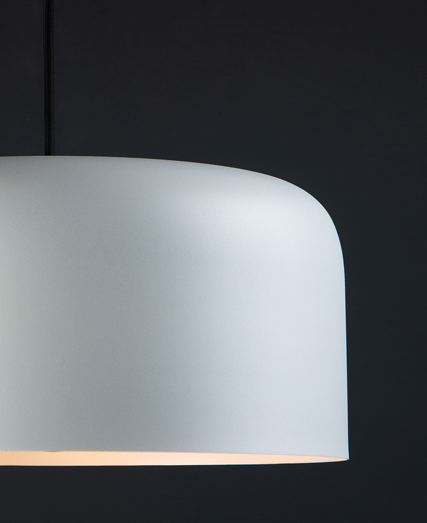 closeup white bodo kitchen pendant lighting suspended from black fabric cable against black wall