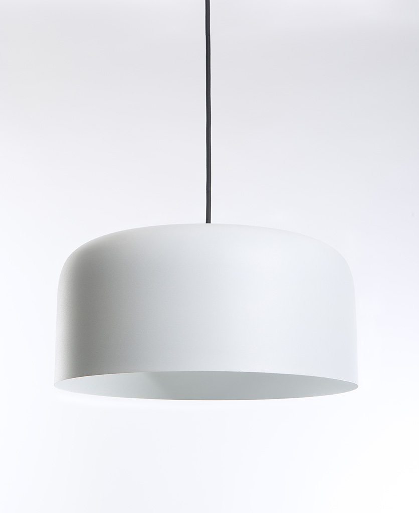 white pendant light suspended from black fabric cable on white background