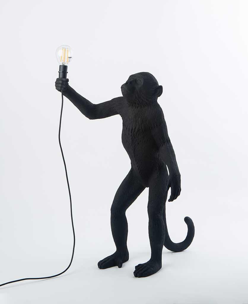Buddy standing monkey black resin table lamp holding light bulb on white background