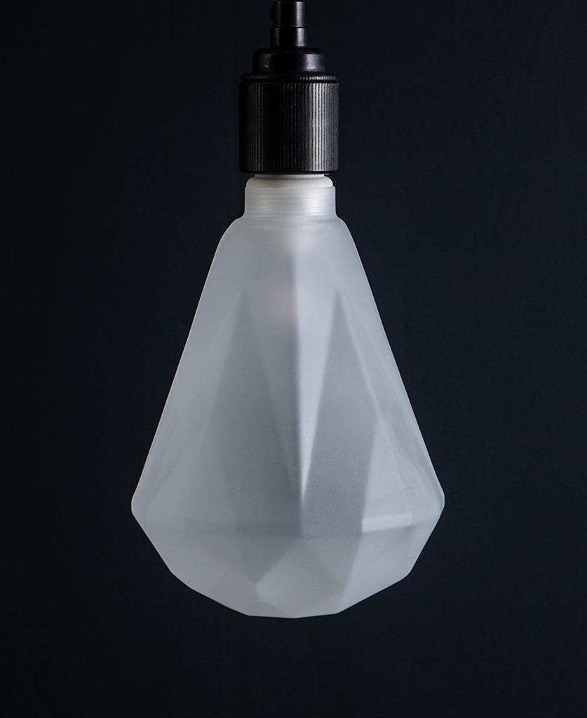 lit frosted diamond geometric light bulb against black background