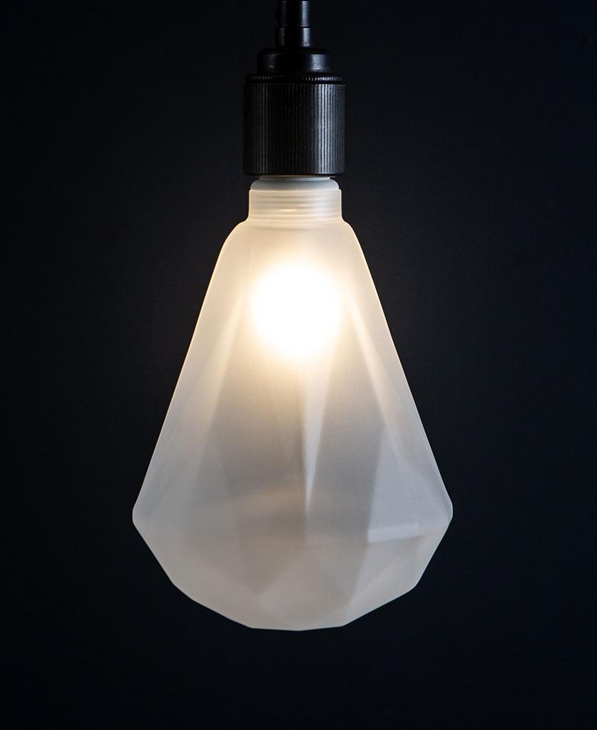 lit frosted diamond geometric decorative led light bulbs against black background