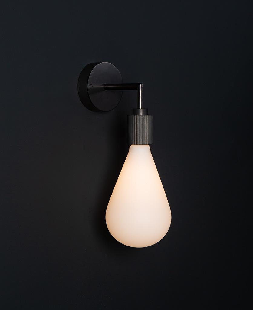 Grosvenor antique black lit wall light fixture against black background