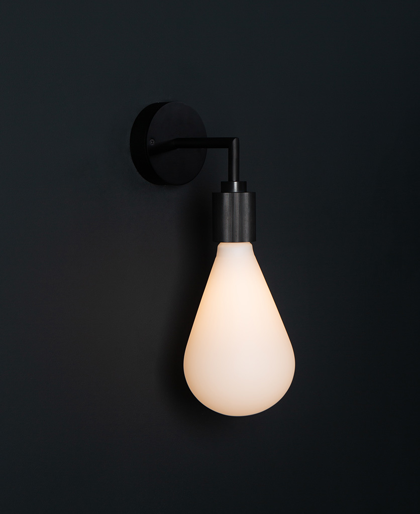Grosvenor black lit wall light fixture against black background