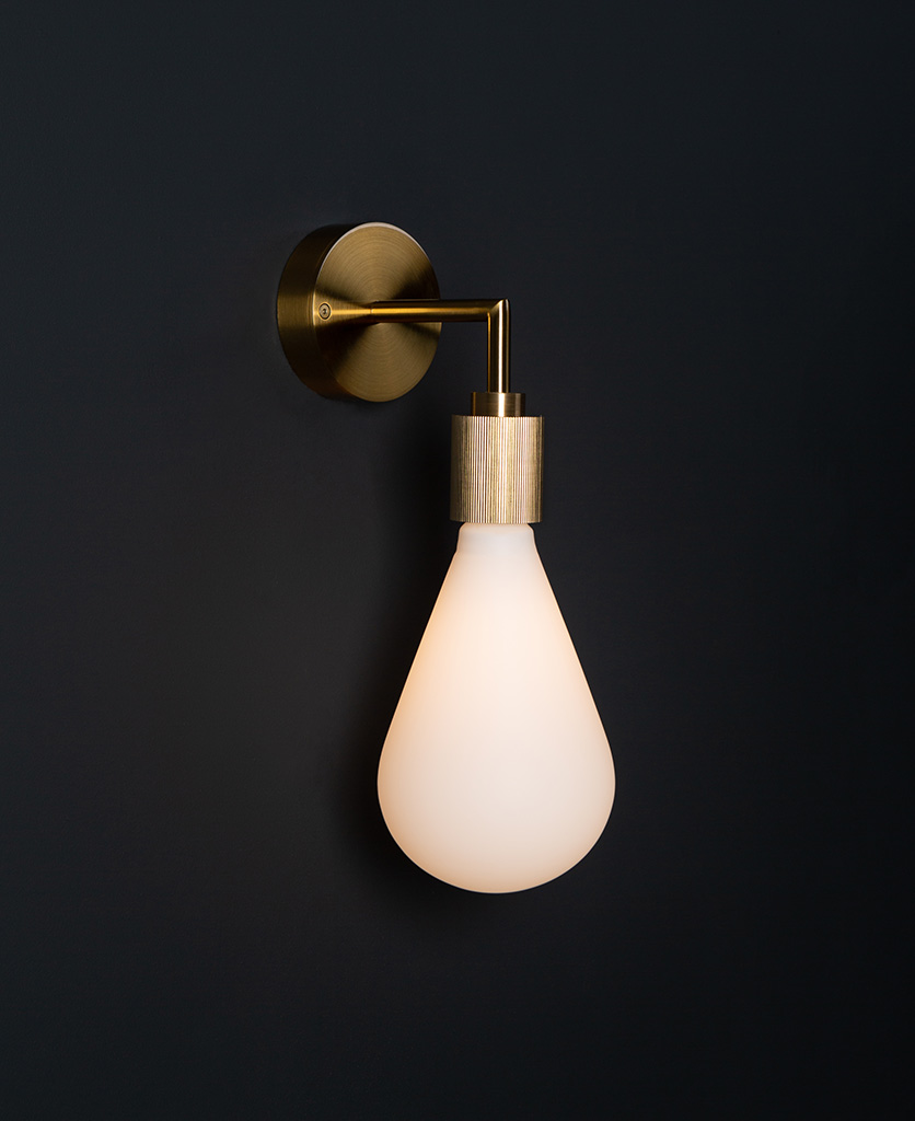 Grosvenor gold lit wall light fixture against black background