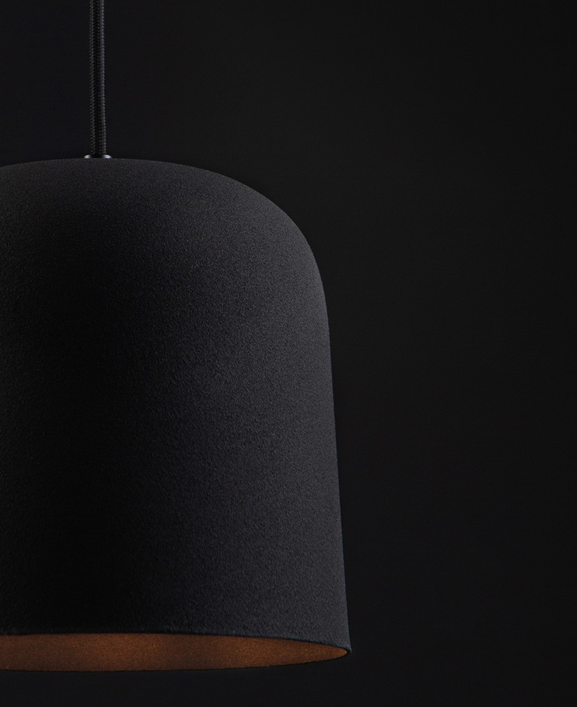 closeup of visby black kitchen pendant lights suspended from black fabric cable against black background