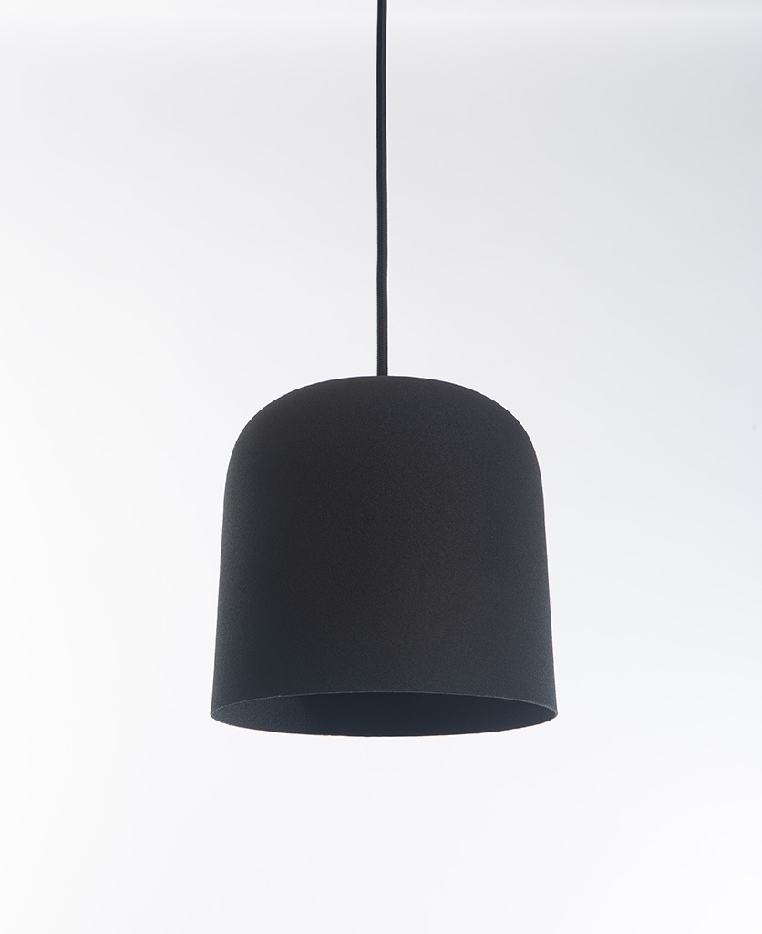 closeup of visby black kitchen pendant lights suspended from black fabric cable against white background